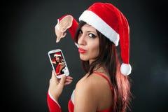 Härlig sexig flicka som bär Santa Claus kläder med smartphonen Royaltyfri Fotografi