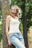 Härlig sexig flickablondin i parkera i solglasögon med stora fylliga kanter som står nära ett träd Royaltyfri Bild