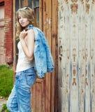 Härlig sexig flickablondin nära ett gammalt övergett hus i solglasögon med stora fylliga kanter i jeans och ett omslag Royaltyfria Foton