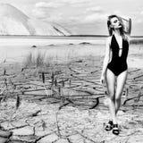 Härlig sexig gullig flicka i en modefors i en baddräkt i torr sprucken jord för öken i bakgrunden av bergen Arkivfoto