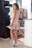 Härlig sexig kvinna i den eleganta beigea trendiga klänningen som poserar i studio fotografering för bildbyråer
