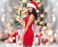 Härlig sexig kvinna i den santa hatten och röd klänning Arkivbild
