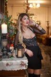 Härlig sexig kvinna i elegant svart klänning med Xmas-trädet i bakgrund Stående av den trendiga blonda flickan som inomhus posera Fotografering för Bildbyråer
