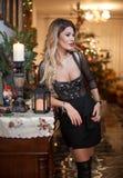 Härlig sexig kvinna i elegant svart klänning med Xmas-trädet i bakgrund Stående av den trendiga blonda flickan som inomhus posera Arkivbild