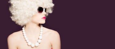Härlig sexig kvinna i en blond afro peruk Royaltyfri Bild