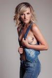 Härlig sexig kvinna i jeans och en waistcoat med en tatuering på sidan av en fågelkolibri i studion royaltyfri fotografi
