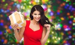 Härlig sexig kvinna i röd klänning med gåvaasken Arkivfoto