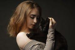 Härlig sexig kvinna i svart hållande svart katt Härlig ung och stilfull kvinna som rymmer en grå katt N?ra ?vre konst arkivbilder