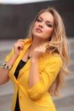 Härlig sexig kvinna med att posera för gult omslag som och för blont hår är utomhus- fashion flickan Arkivbild