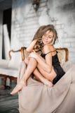 Härlig sexig kvinna med blont hår i elegant svart klänningsammanträde på fåtöljen i rum Royaltyfria Foton