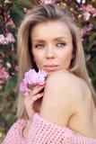 Härlig sexig kvinna med blont hår som poserar i sommarblomninggummin Arkivfoto