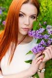 Härlig sexig kvinna med brännhett styrehår med ögon av en räv i trädgården med lilor Royaltyfria Foton