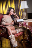 Härlig sexig kvinna med exponeringsglas av vin som läser ett boksammanträde på stol Royaltyfria Foton