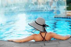 Härlig sexig kvinna som kopplar av i simbassängvatten Flicka med sund brunbränd hud, ursnygg framsida, modemakeup royaltyfri foto