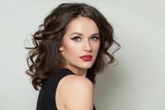 Härlig sexig kvinna som ser kameran Nätt modell med makeup och den bruna ståenden för lockigt hår arkivbilder