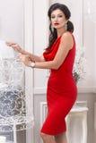 Härlig sexig lyxig brunn-ansad ung kvinna i röda åtsmitande örhängen för en klänning med diamanter och standinen för svart hår fö Royaltyfria Bilder
