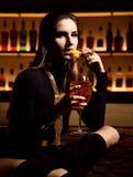 Härlig sexig modebrunettkvinna i stångrestaurang som kopplar av dricka den orange aperolspritcoctailen royaltyfri fotografi