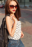 Härlig sexig modeflicka i trendig solglasögon i jeans som går runt om staden på solnedgången arkivbild