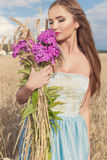 Härlig sexig slank flicka i en blå klänning i fältet med en bukett av blommor och öron av havre i hans händer på solnedgången på  Arkivfoton