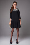 Härlig sexig ung affärskvinna med aftonsminket som bär en klänning och hög-heeled skor och en liten svart handväska, affär Royaltyfri Foto