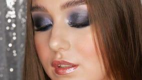 Härlig sexig ung flicka med hår för blåa ögon för smink för afton långt rökiga och kosmetiska kulöra kontaktlinser som  lager videofilmer