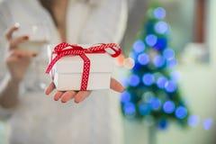 Härlig sexig ung kvinna i vitt tröjasammanträde bredvid trädet för vit jul som rymmer gåva Royaltyfri Bild