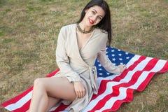 Härlig sexig ung kvinna med den klassiska klänningen som ner ligger på amer Royaltyfri Fotografi