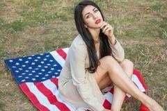 Härlig sexig ung kvinna med den klassiska klänningen som ner ligger på amer Arkivfoto