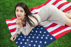 Härlig sexig ung kvinna med den klassiska klänningen som ner ligger på amerikanska flaggan i parkera modemodell som rymmer oss at Arkivfoto
