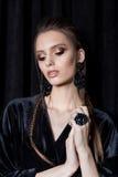 Härlig sexig ung kvinna med mörkt hår som flätas med ljusa makeup- och modebizhuterieykerörhängen och cirkeln, modesmycken arkivbild