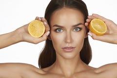 Härlig sexig ung kvinna med perfekt sund hud och skuldror för lång brun hårdagmakeup som kala rymmer den orange citrongrapefrukte Royaltyfri Fotografi