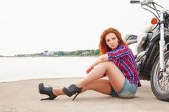 Härlig, sexig ung kvinna på en motorcykel Royaltyfri Bild