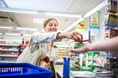 Härlig shopping för ung kvinna i en livsmedelsbutik royaltyfria bilder