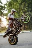 Härlig sideview av cyklistridningmotorcykeln i extrem väg arkivfoton