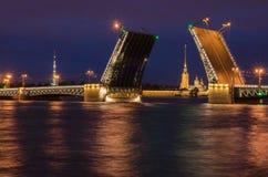 Härlig sikt av aveln av broar i natten St Petersburg från invallningen av Neva River Royaltyfri Bild