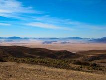 Härlig sikt av de steniga bruna och blåa bergen mot den ljusa blåa himlen arkivbilder