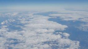 Härlig sikt av den blåa himlen med moln från hyttventilen av nivån under flyget arkivfoton