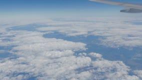 Härlig sikt av den blåa himlen med moln från hyttventilen av nivån under flyget arkivfoto