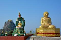 Härlig sikt av den guld- Buddhastatyn med monteringen Popa, Myanmar Arkivbilder