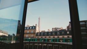 Härlig sikt av den iconic Eiffeltorn i Paris till och med det öppna sommarmorgonfönstret, tunnelbanadrev som förbigår hus arkivfilmer