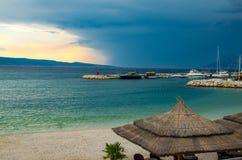 Härlig sikt av den sandiga stranden med sugrörparaplyer, port och den lilla fyren på stenpir framme av den Brac ön på helgdagsaft arkivfoton