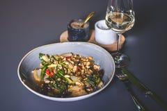 Härlig sikt av en maträtt med jordnötter nära ett exponeringsglas av vitt vin Arkivbilder