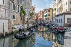 Härlig sikt av en typisk venetian kanal, Venedig, Italien, med ett par på en gondol som tar bilder och gör videoen royaltyfri bild