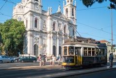 Härlig sikt av Estrela basilikafasad och historisk gul spårvagn 28 på spårvagnstoppet royaltyfri fotografi