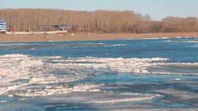 Härlig sikt av isdrivan på floden på våren Sandig strand med träd gå för strandfolk arkivfilmer