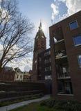 Härlig sikt av kyrkan och husen i den holländska staden av Vlaardingen på en molnig dag royaltyfri bild