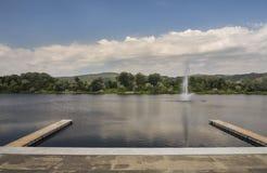 Härlig sikt av Silver Lake med två träpir och springbrunn Royaltyfri Foto