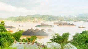 Härlig sikt av trafik av bogserbåtar som drar pråm av kol på den Mahakam floden, Samarinda, Indonesien arkivbild