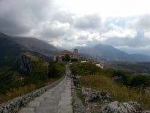 Härlig sikt av vägen till kyrkan och bergen och den mulna himlen med moln, Maratea Italien royaltyfri foto