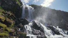 Härlig sikt av vattenfallet Höga klippor som täckas med grön mossa, solen, skiner i ramen, vattendroppar faller på